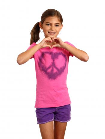 A cute young girl making a heart symbol