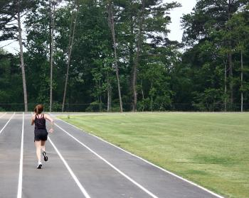A cute young girl on a track field