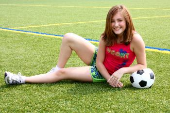 A cute young girl posing with a soccer