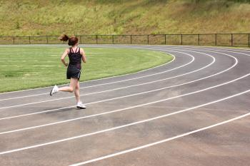 A cute young girl running on a track