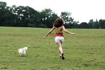 A cute young girl running with her dog