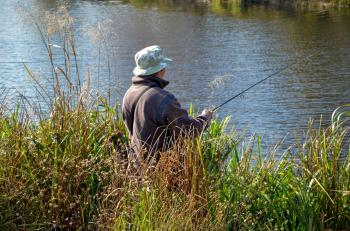 A fisherman stands on the shore in a thicket of grass