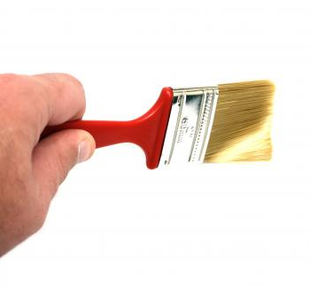 A hand holding a paint brush