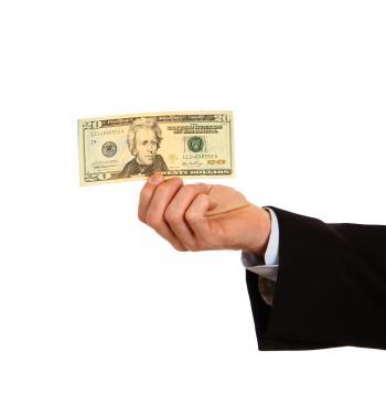 A hand holding a twenty dollar bill