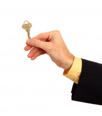 A hand in a business suit holding a key