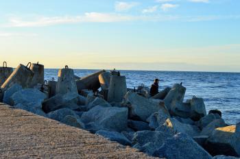 A man sits among tetrapod breakwater on the Baltic Sea