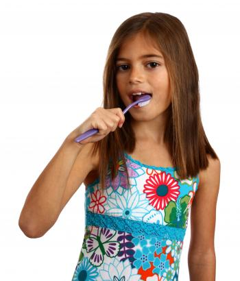 A pretty young girl brushing her teeth