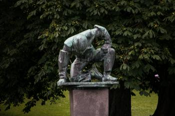 A sculpture of tired or humble man