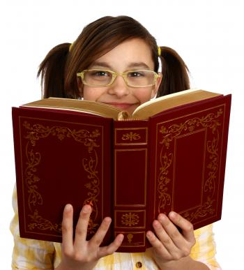 A smart girl with glasses reading a book