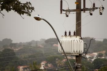 A streetlight and transformer post in the rain