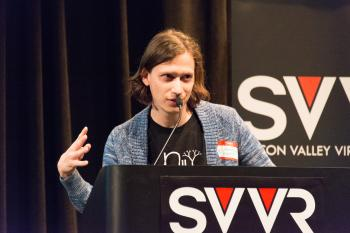 Aaron Lemke of Unello Design giving 60 Second Pitch at SVVR (right hand raised and spread)
