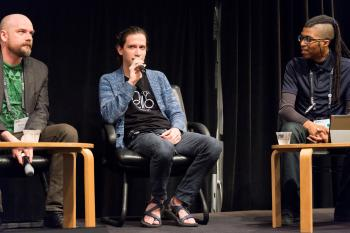 Aaron Lemke (Unello Design) discussing at indie dev panel at SVVR (full body view looking forward at audience with Denny Unger of Cloudhead Games on left and Cymatic Bruce on right)