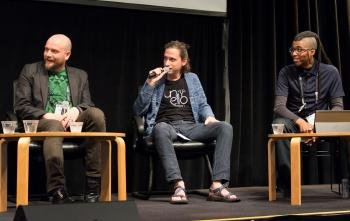 Aaron Lemke (Unello Design) discussing at indie dev panel at SVVR (full body view with Denny Unger of Cloudhead Games on left and Cymatic Bruce on right, all looking stage right)