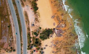 Aerial Photo of Seashore Near Two Lanes of Wide Road