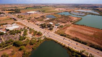 Aerial Photography of an Open Road With Cars Near City and Lake during Daytime