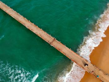 Aerial Photography of Brown Boardwalk Near Green Water on Beach