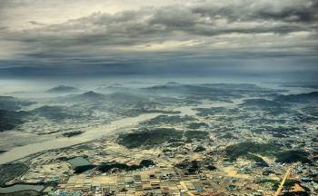 Aerial View Photo of Urban Area and Mountain Range in the Distance Under Gray Cloudy Sky