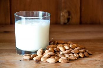 Almond milk with almonds on wood