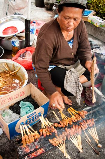 Asian woman selling sate on the street