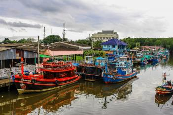 Assorted Color Boats on Body of Water Beside Houses and Trees Under White Sky at Daytime