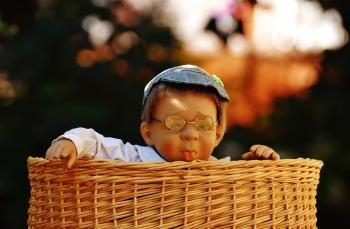 Baby Doll Wearing Eye Glasses Inside the Brown Wicker Basket