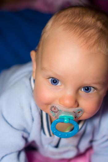 Baby on Blue Romper Biting Pacifier