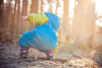 Baby Wearing Blue and Green Rain Coat Picking Brown Dead Tree Branch during Daytime