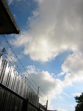 Barb wire fence against a cloudy sky