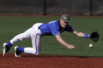 Baseball Player Wearing Blue and White Jersey Catching Baseball