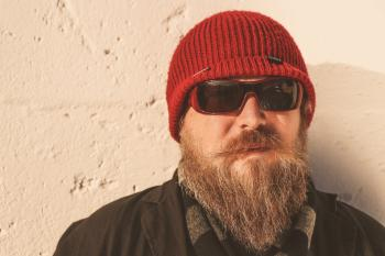 Bearded Man Wearing Red Beanie Cap, Sunglasses ,and Black Jacket