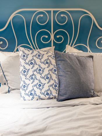 bed with blue linen in the bedroom