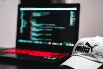 Black and Red Laptop Computer Beside White Puma Curve Brim Cap