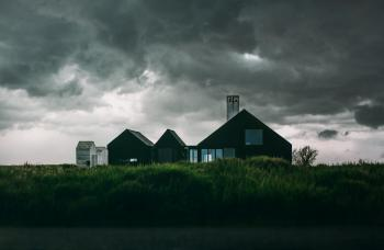 Black and White House Under Thick Clouds