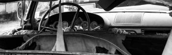 Black and white photo of an abandoned car dashboard
