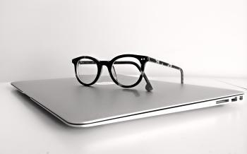 Black Frame Eyeglasses on Silver Macbook Air