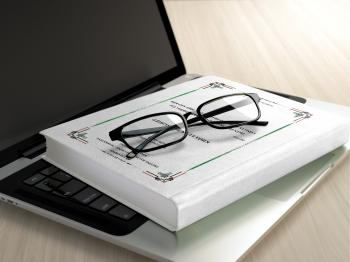 Black Frame Eyeglasses on White Book