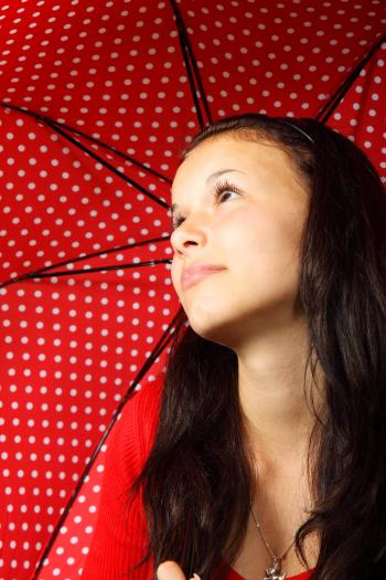 Black Haired Woman in Red Sweater Wearing Silver Dog Pendant Necklace Holding Black Red White Polka Dotted Umbrella