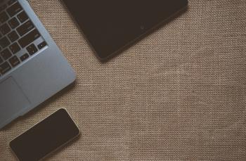 Black Ipad Near Macbook on Brown Textile
