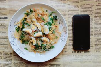 Black Iphone 5 Near Plate of Pasta Dish