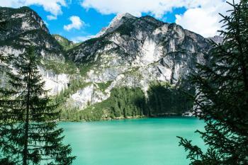 Black Mountain Near Green Body of Water Under Blue Sky