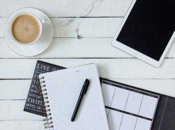 Black Pen on White Writing Spring Notebook Between White Ipad and White Ceramic Mug With Latte on White Plate