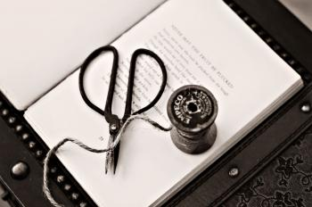 Black Scissors Near Thread Reel on White Book Page