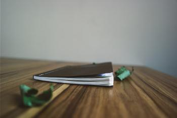 Black Small Notebook on Brown Wooden Surface