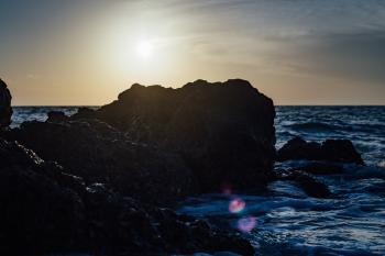 Black Stones on Sea Side during Sunset