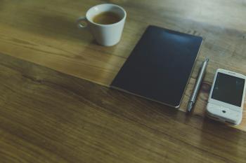 Black Table Computer Beside White Mug