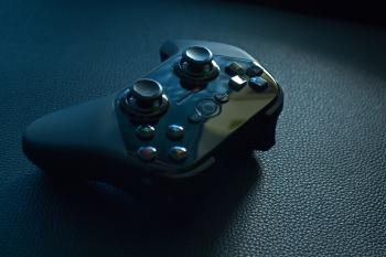 Black Wireless Game Controller on Black Leather