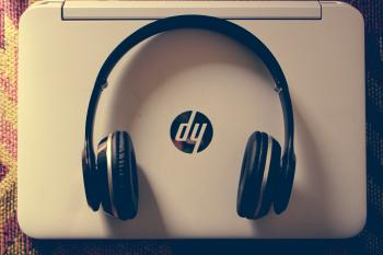 Black Wireless Headphone Near White Hp Laptop