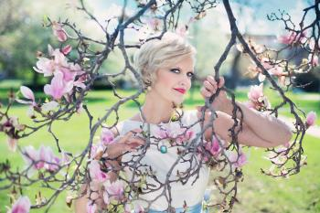 Blond Haired Woman Posing on Leafless Pink Flowered Tree