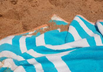 Blue and white towel on the sand
