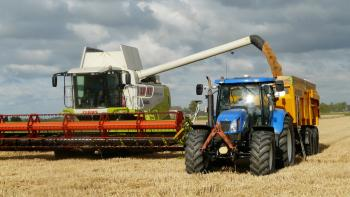 Blue Tractor Next to White Farm Vehicle at Daytime